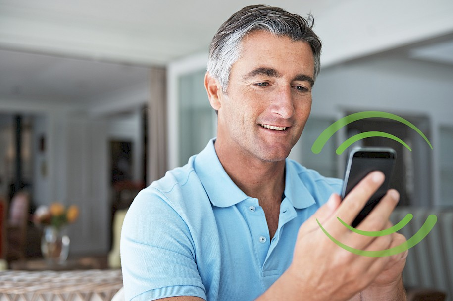 man in blue shirt holding smartphone