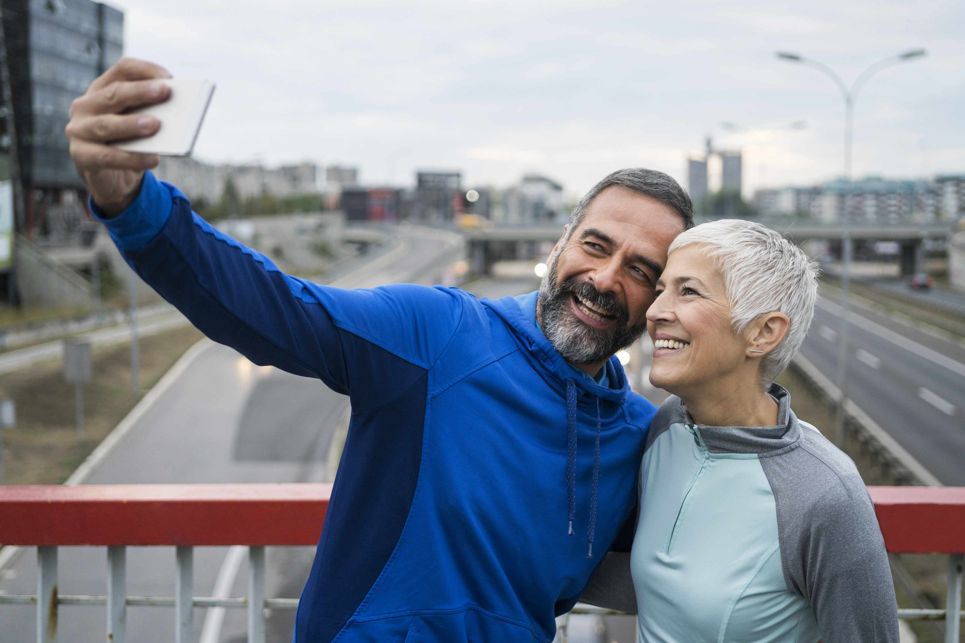 Man and woman taking selfie on bridge
