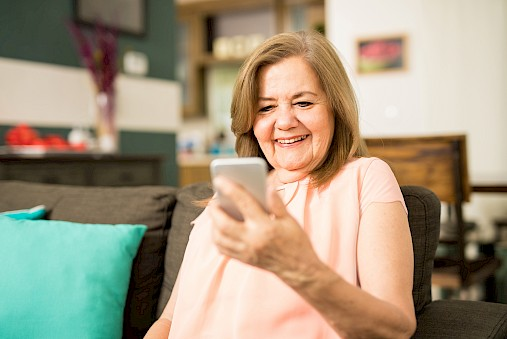 Woman sitting at home, smiling and looking at phone.