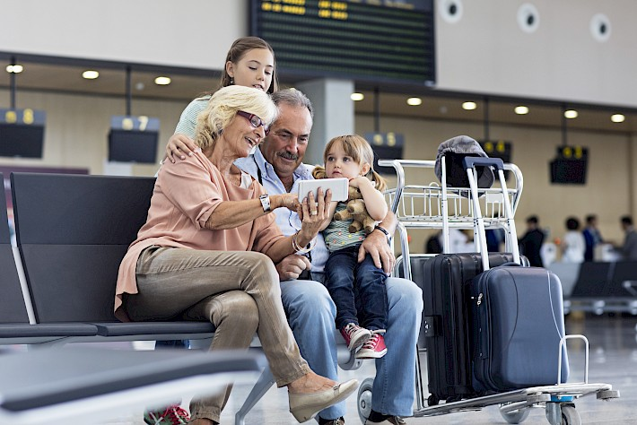 Grandparents taking selfie with grandkids at airport