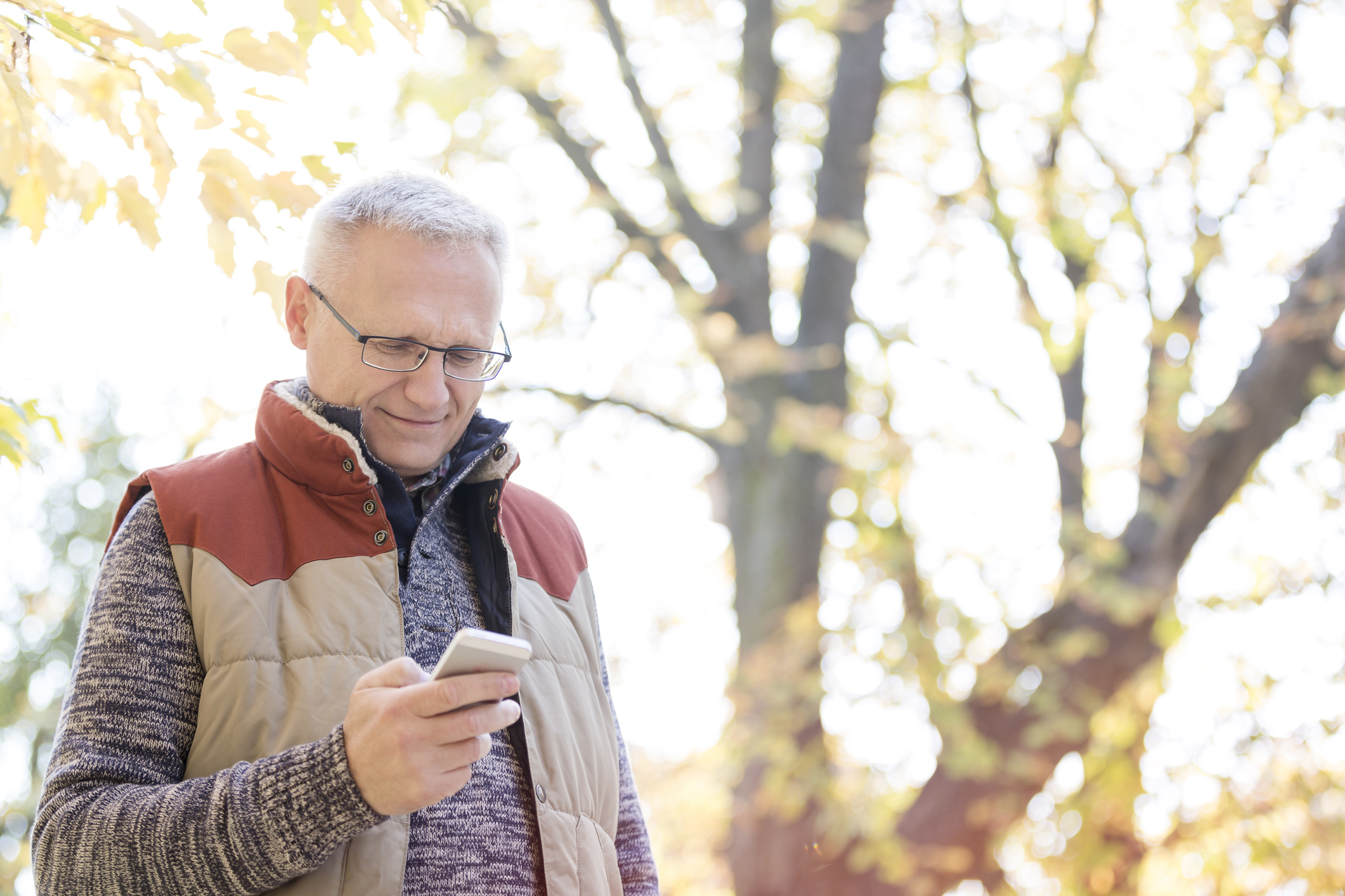 Man in jacket using phone outdoors