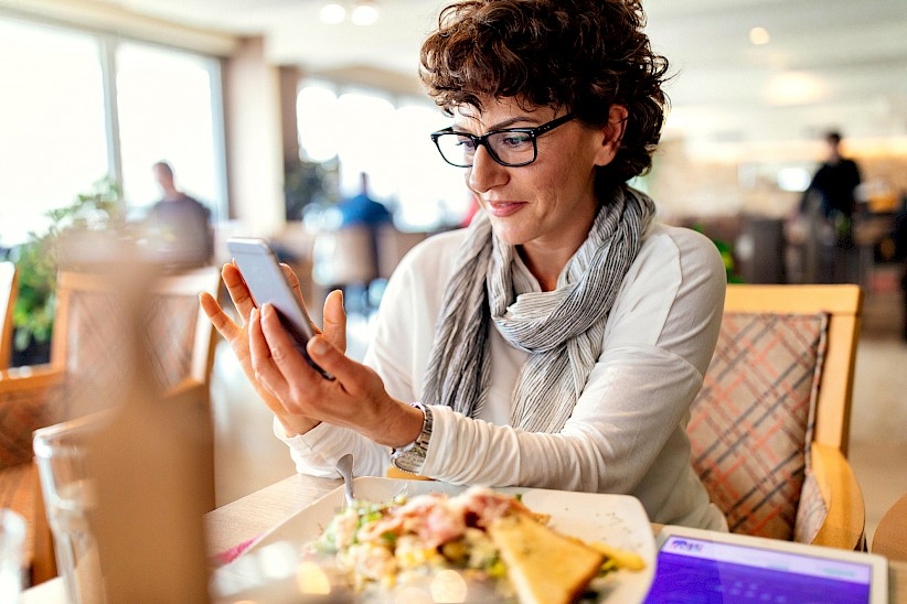 Woman using smartphone at restaurant