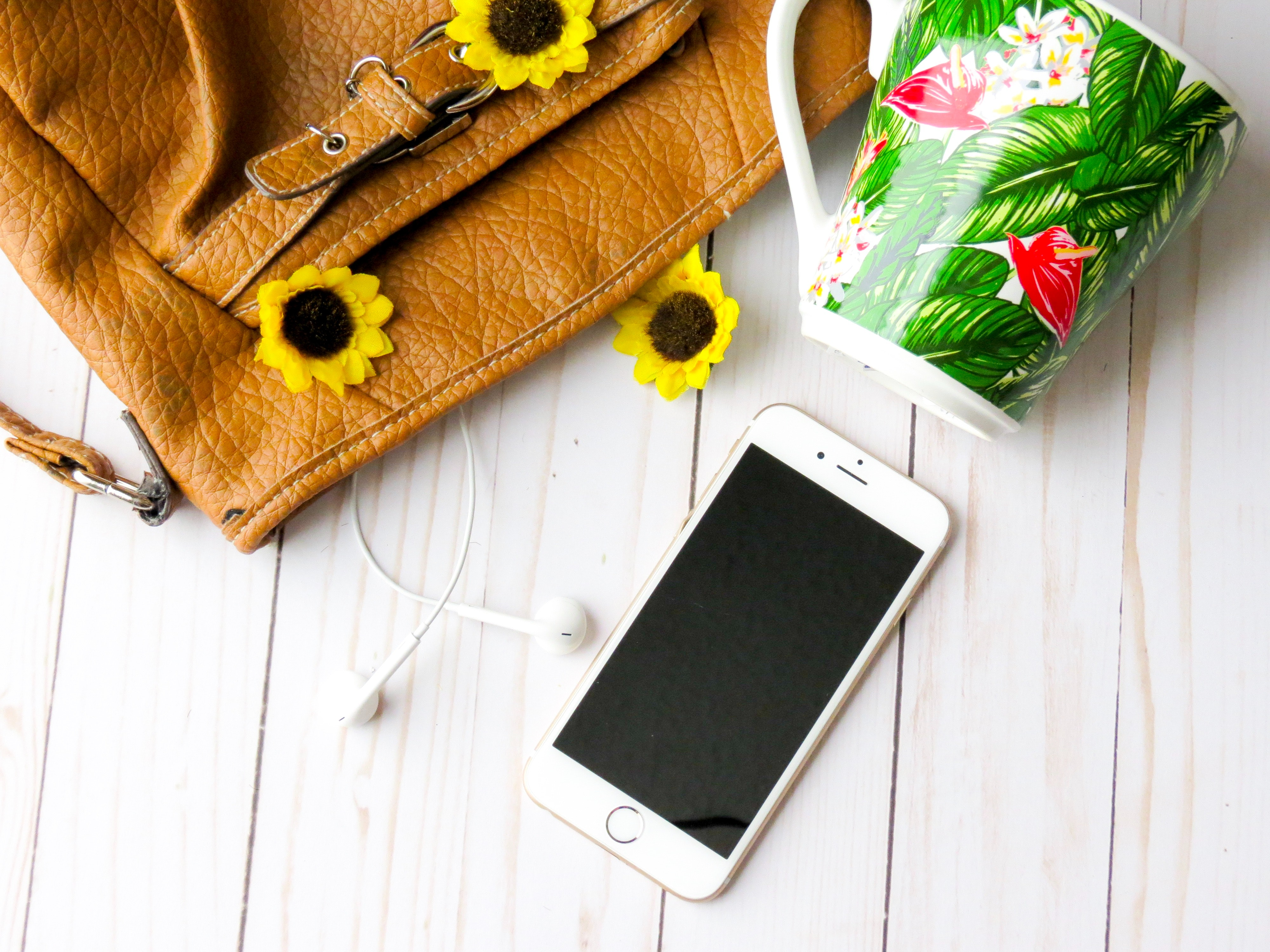 iPhone with flowers, bag, and floral mug