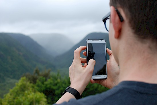 Man taking a nature photo with his cell phone